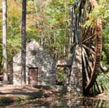 Photo shows a large wooden water wheel near a stone structure and creek.