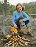 Photo shows a girl roasting a hot dog in the flames of a campfire of burning wood.