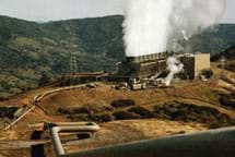 Photo shows a large building on a hilltop with many pipes to it and water vapor emissions leaving the structure.