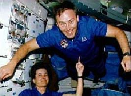 Photo shows one astronaut balancing another astronaut on her pointer finger in microgravity (his chest and body is balanced on her one finger ─ literally!).