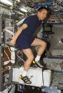 A photograph showing an astronaut ride an exercise bike while in outer space.