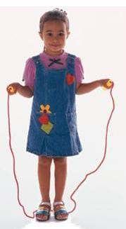 A photograph of a young girl standing still and holding a jump rope.