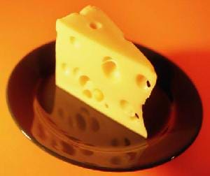 A photograph of a wedge of Swiss cheese on a brown plate.