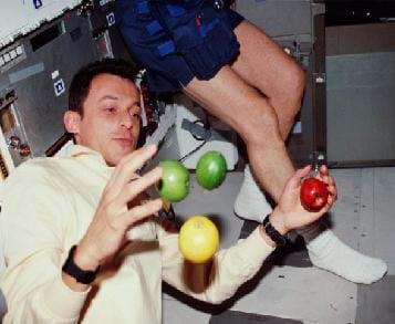 Photo shows an astronaut attempting to hold onto apples while in space. The apples are floating around him.