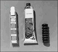 Photo shows three items. The tube looks like a toothpaste tube, and one of the snacks looks like a small stack of eight mini-car tires. The other snack appears to be a set of small cubes placed in a metal holder.