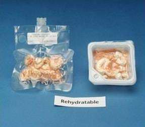 "Photo shows two different packages of rehydratable shrimp cocktail. The package on the left is clear and vacuum sealed, and has a short tube placed in the side for adding water. The package on the right is a translucent plastic square box, with the lid removed. A sign below the packages reads: ""Rehydratable."""