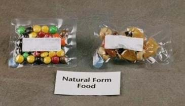 "Photo shows colorful round candies, and trail mix encased in plastic. A nearby sign reads: ""Natural Form Food."""