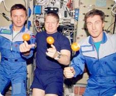 Photo shows three astronauts balancing floating oranges on their right pointer fingers.