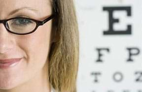 A photograph shows a young woman with glasses and a portion of an eye chart in the background.