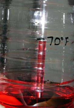 Photo shows a water bottle with red liquid in the bottom and a straw sticking in it. The red liquid has risen part way up the straw and where it ends is marked as 70°F.