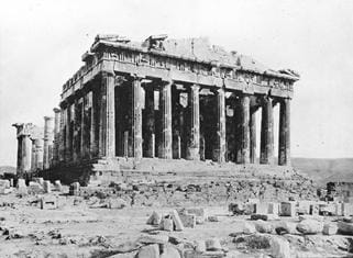 A black and white photograph of the Greek Parthenon, a crumbling structure composed of many columns.