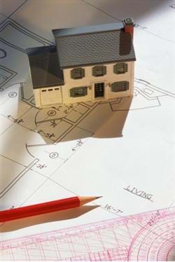 A model of a house and the accompanying blueprint. Shown are a miniature, 2-story house, sitting on a blueprint, and next to a pencil and architect's ruler.