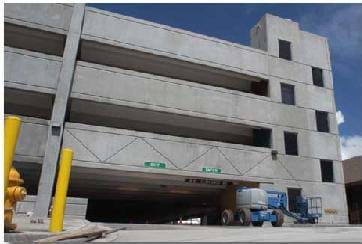 A photograph shows a four-story parking garage made of concrete.