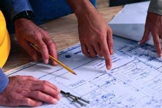 A photograph of architects pointing to (and discussing) a blueprint.