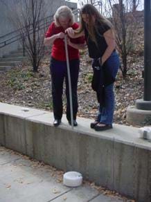 A photograph shows an outside egg drop testing station. Two women stand on a bench. One holds a yardstick while the other is about to release an egg from about six feet above a prototype foam landing pad.