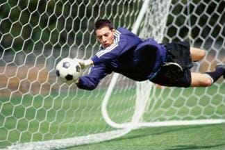 Action photograph of a soccer goalie stopping a shot on goal. The goalie appears to be flying through the air to stop the ball.