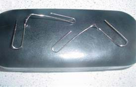 A photo shows two bent paperclips with the two curved ends pulled away from each other at right angles.