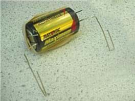 A photo shows a battery with a looped paperclip on each end. A rubber band stretches lengthwise across the battery to secure the two paperclips.