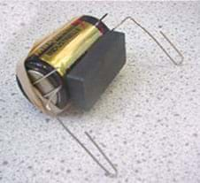 A photo shows the ceramic magnet on the side of the battery, along with the paperclips and rubber band.