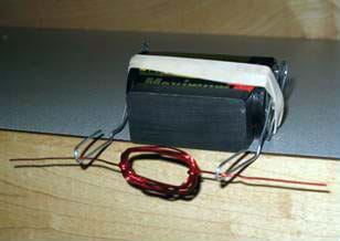A photo shows a magnet and battery together, with the rubber band holding the bent paperclips in place, all perched on a table edge. The wire coil rests across the paperclip cradles, which extend beyond the table edge.