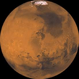 A round image of Mars shows its red surface and northern polar ice cap.