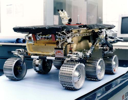 Photo shows a six-wheeled robot sitting on a tabletop.