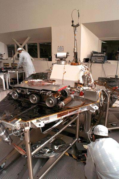 A photo of  NASA engineers assembling the Mars Pathfinder lander and the Sojourner rover in a lab at NASA's Jet Propulsion Lab (JPL).