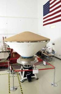The aeroshell in a NASA lab. The brown colored heat shield is on top while the white backshell is on the bottom.