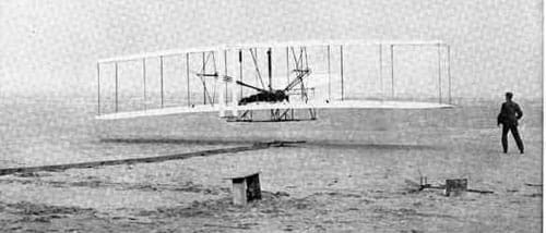Black and white photograph of a simple bi-wing aircraft with one man lying face down, head forward in the center of the open plane and a second running nearby.