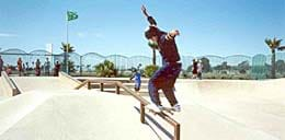 A photograph showing a skateboarder doing a rail slide at a public skate park in San Diego. With both hands up in the air for balance, he stands with both feet on his skateboard, which is on the top of a horizontal hand rail.