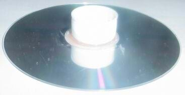 A photo shows a plastic bottle cap attached with the top of the lid glued to the middle of a round, silvery CD.