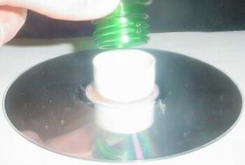 A photo shows placement of the cut-off plastic bottle top screw end into the bottle cap, which is glued to a compact disc.