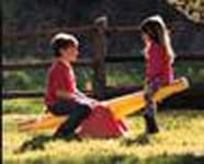 A photograph of two young children playing on a seesaw, one child up, one child down, in the sunshine in a grassy yard.