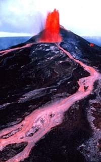 Photo of red lava spewing out of a volcano vent and flowing down its slope.