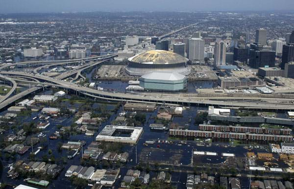 An aerial photograph shows flooded streets, buildings, highways, skyscrapers and superdome.