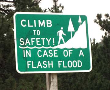 A photograph shows a green and white road sign with the message: Climb to safety in case of a flash flood.