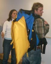Photo shows a young man wearing a blue backpack with a yellow, pillow-shape sticking out from it.