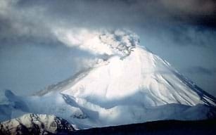 Photo shows white and gray dirt and ash being ejected from the peak of a tall, snow-covered mountain.
