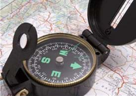 A photograph shows a compass on a paper map.
