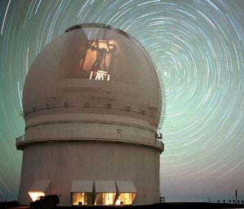 A photograph of an observatory at night with the star trails in the night sky; they look like rings of concentric circles.