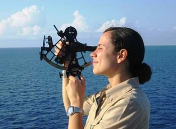 Photo shows a woman on a boat in the ocean using a sextant.