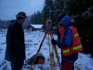 Photo shows a surveyor peering through a theodolite, the optical instrument used for measuring.