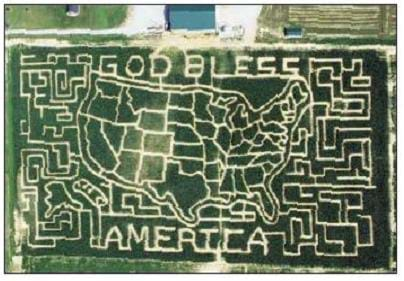 "An aerial photograph of a corn field shows a map of the U.S., the words ""God Bless America,"" and mazes on the outer edges of the field that have been cut into the field. The design was ""mapped out"" using inexpensive software, and then the farmer plowed the field accordingly using data loaded into a GPS receiver."