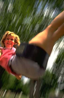 Photo shows a girl swinging.