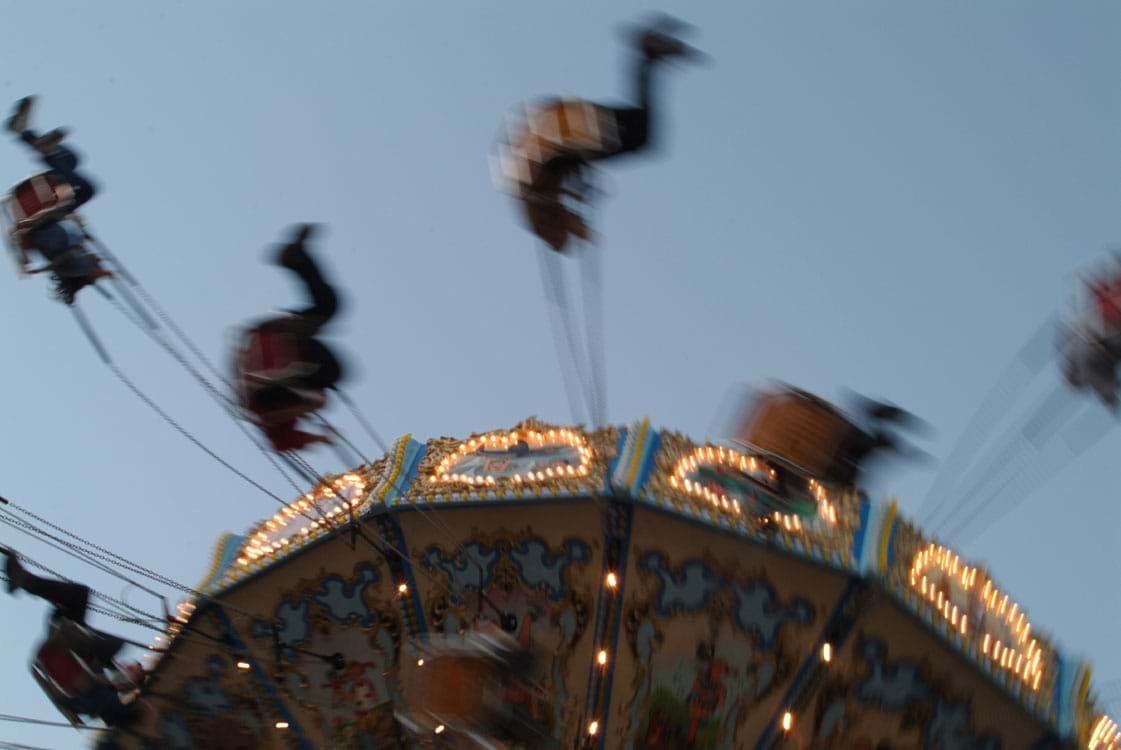 A photo shows seated people swinging and spinning from an amusement park ride that moves in a circle.