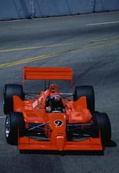 Photo shows a red race car on an asphalt track.