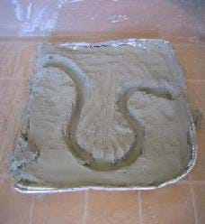 Photo shows a pan of clay with a meandering ditch cut into it.