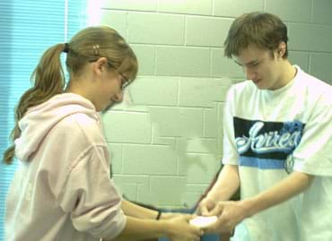 Photo of two students, each pulling on one end of a bar of soap.