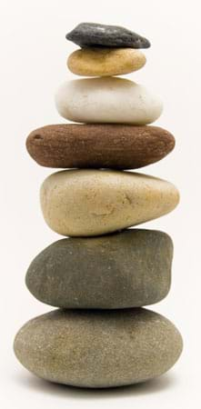 Photo shows a stack of seven various types of rounded rocks.