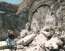 Photo shows two men looking at metal prongs coming through the side of a mountain with a crumbling rock pile in front of them.